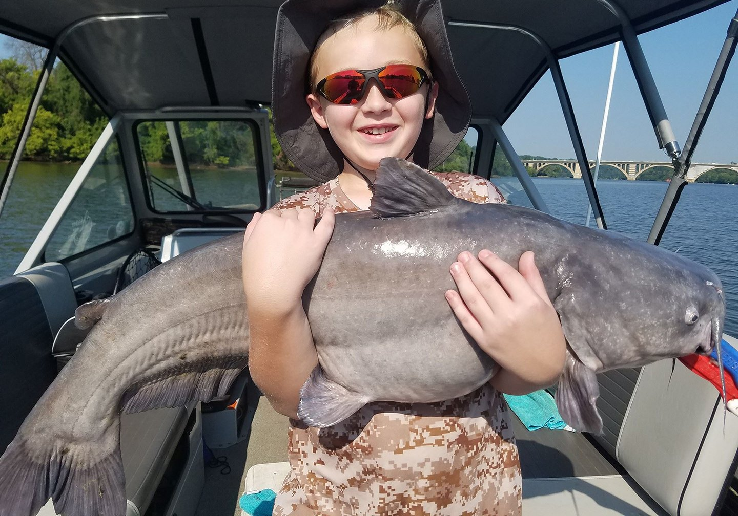 A happy child ion a boat holding a big Blue Cat caught on a catfishing trip.