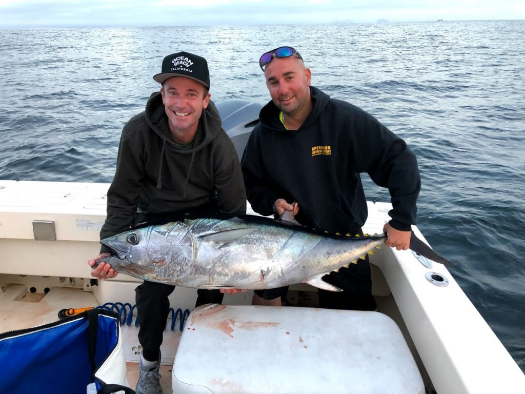 smiling anglers holding a Bluefin Tuna on a fishing boat
