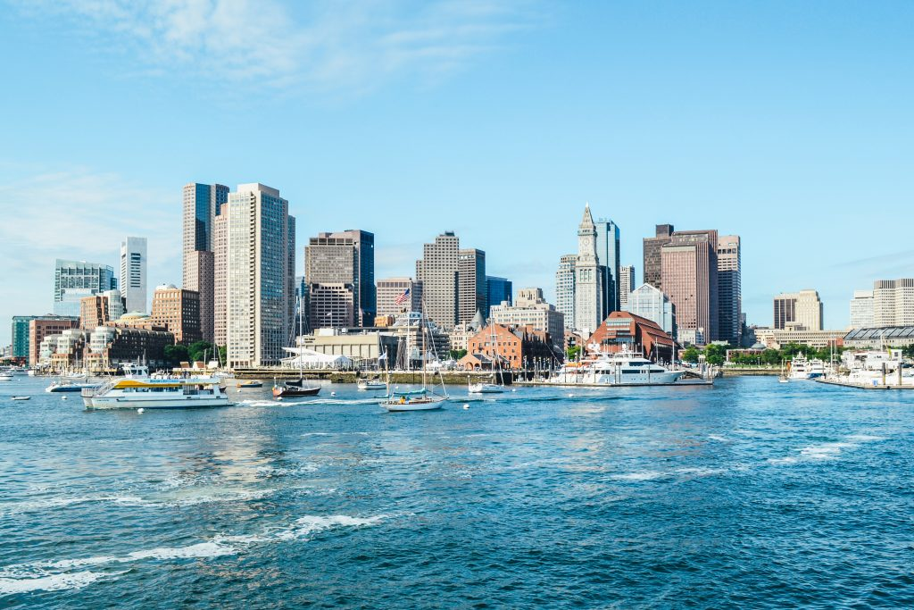 Boston Harbor seen from the water, with sailboats in the sea and the city skyline behind