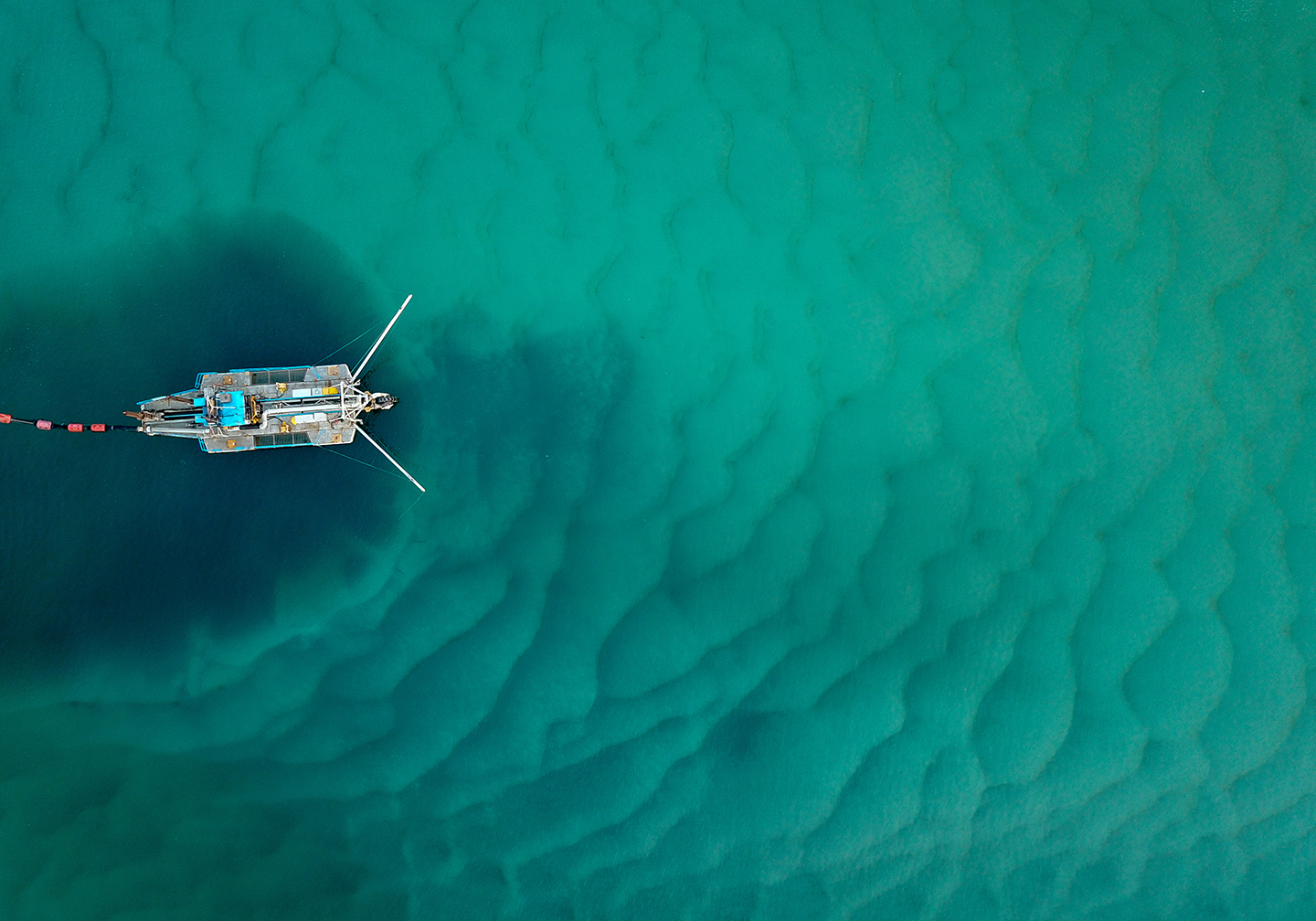 A view from above of a bottom trawler in the ocean. The dark water under the boat shows the destruction of the seafloor.