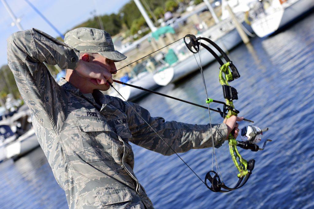 Bowfishing army man aiming down at the water near Tyndall Air Force Base