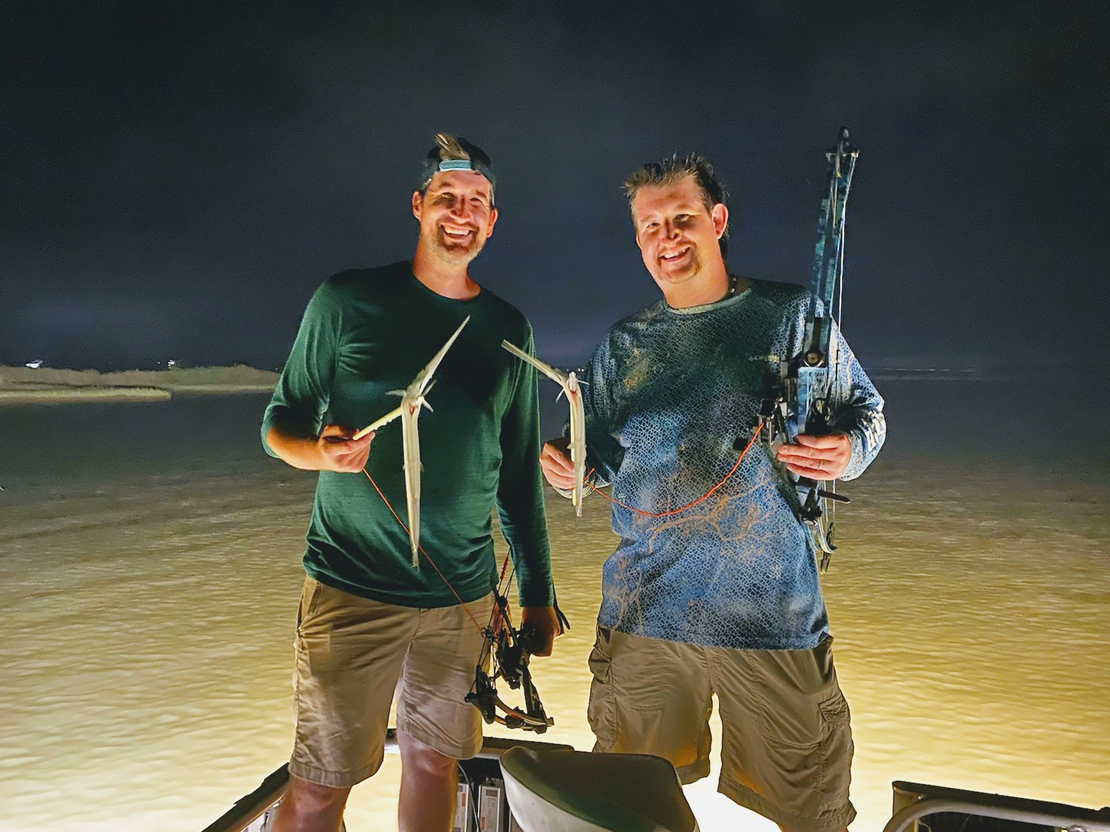 Two men holding bowfishing equipment and a couple of Needlefish while standing on a boat in nighttime