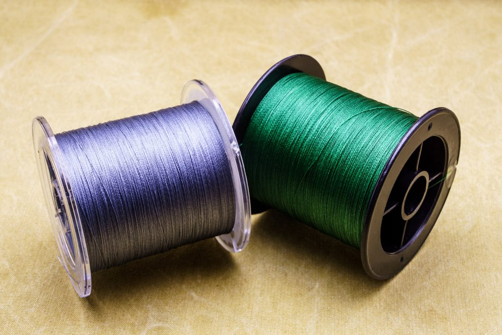 Two spools of braided fishing line, one purple and one green