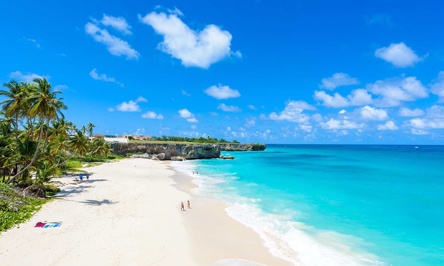 A white sandy beach in Bridgetown, Barbados, with turquoise water and blue sky.