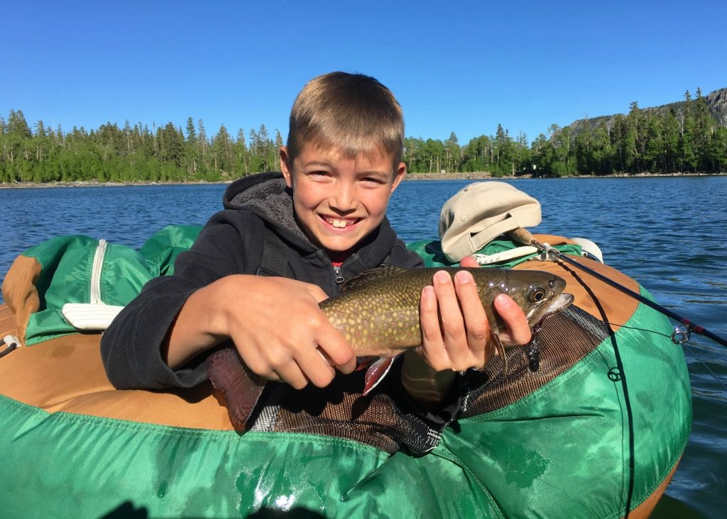 a smiling young angler holding a Brook Trout