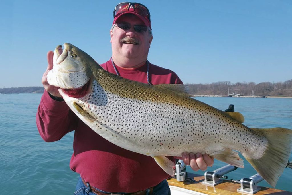 A happy man holds a Brown Trout on a charter boat with water behind him