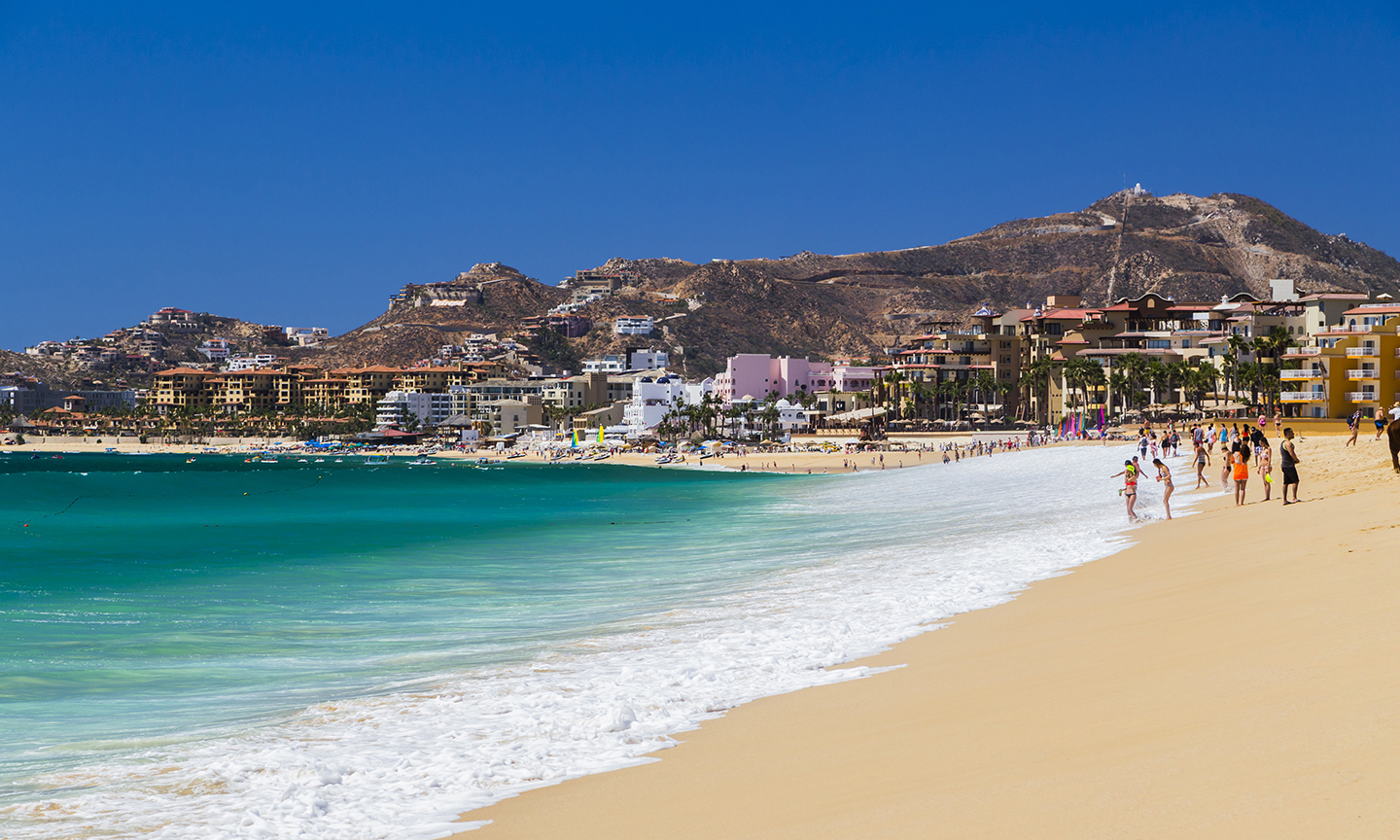 A view along the beach toward Cabo San Lucas, Mexico, with green-blue water to the left and blue sky above.
