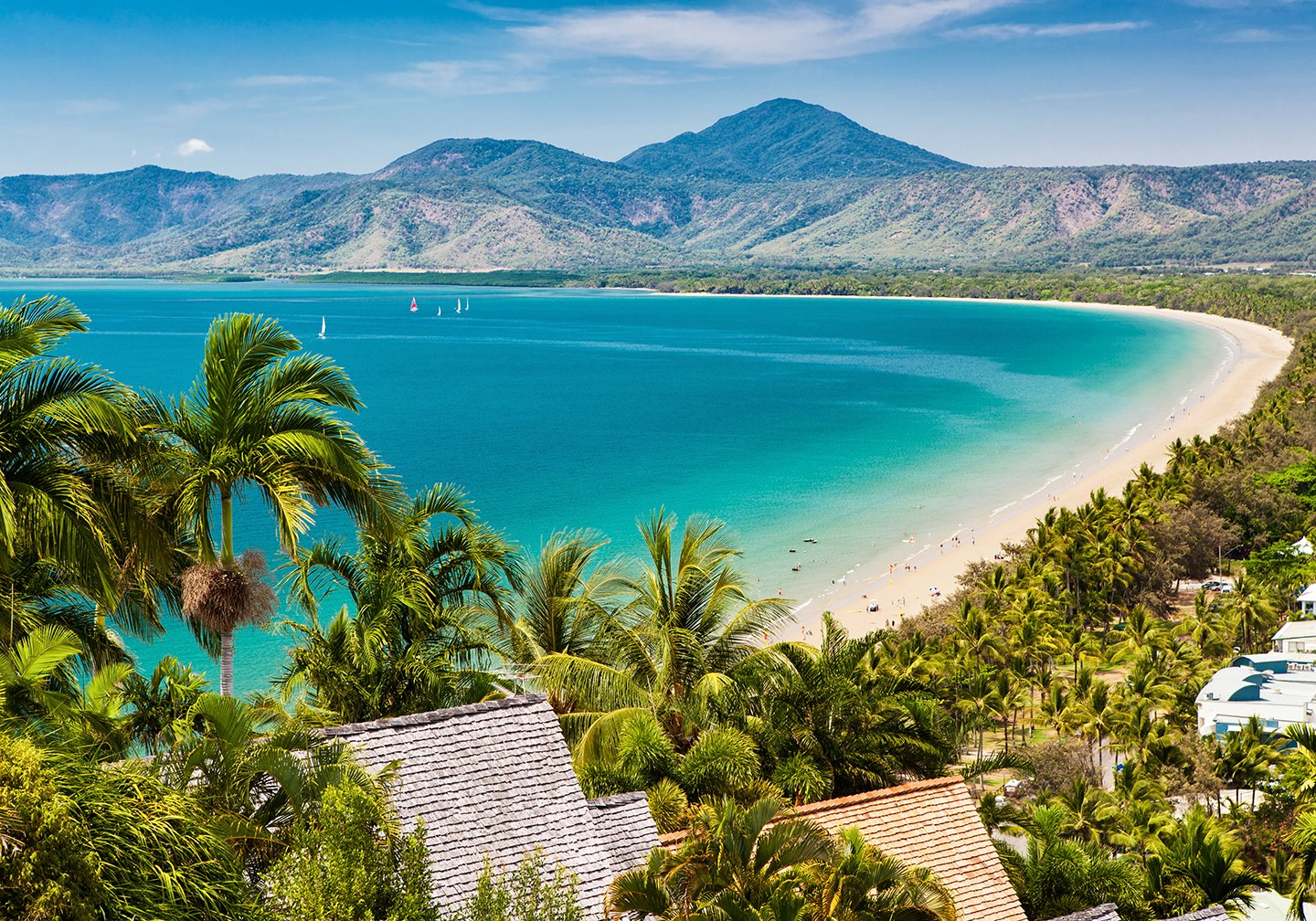 A view of the bay in Cairns, Australia, with green trees, yellow sand, and turquoise water.