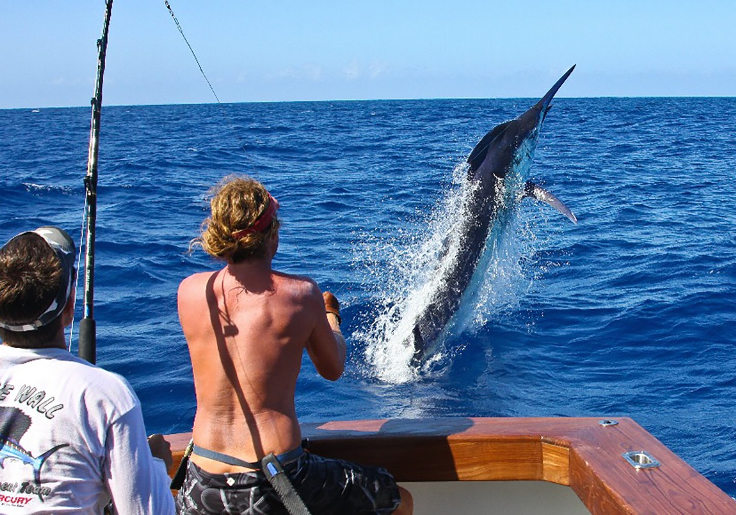 A topless male angler on a charter boat fighting a large Black Marlin which is jumping out of the water.