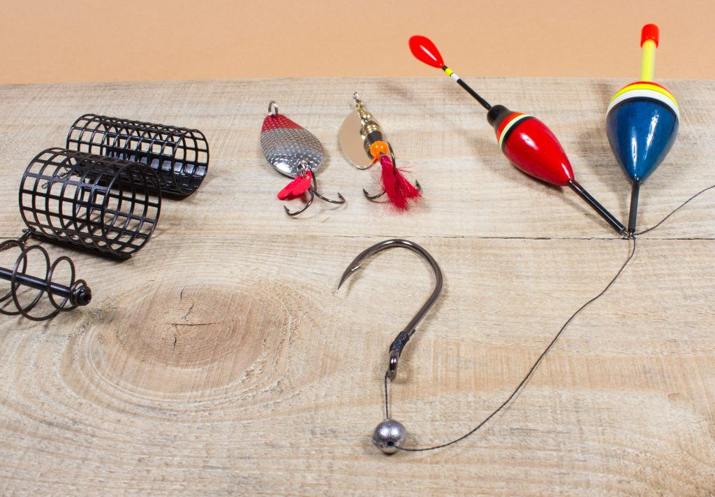 Assorted fishing tackle on a wooden table, with a hook and sinker making a question mark in the middle