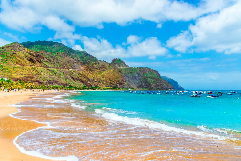 An idyllic beach on Tenerife, Canary Islands, with yellow sand and small fishing boats in bright blue water