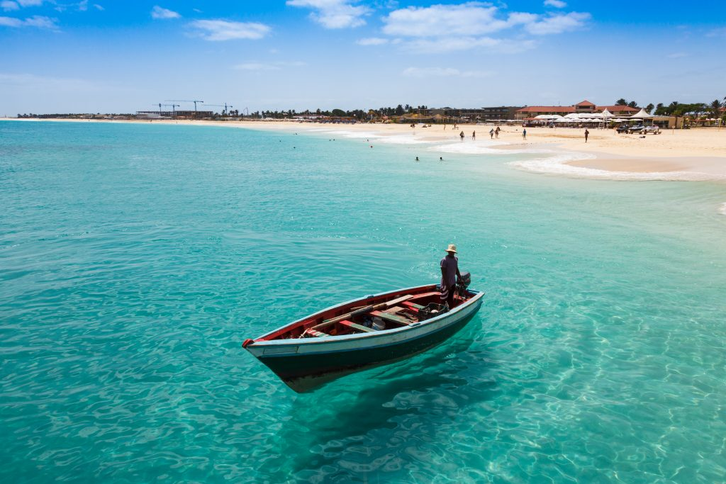 Fisherman on a boat in turquoise water, white sand beach and people swimming behind him, Cape Verde Islands, fishing destinations in africa