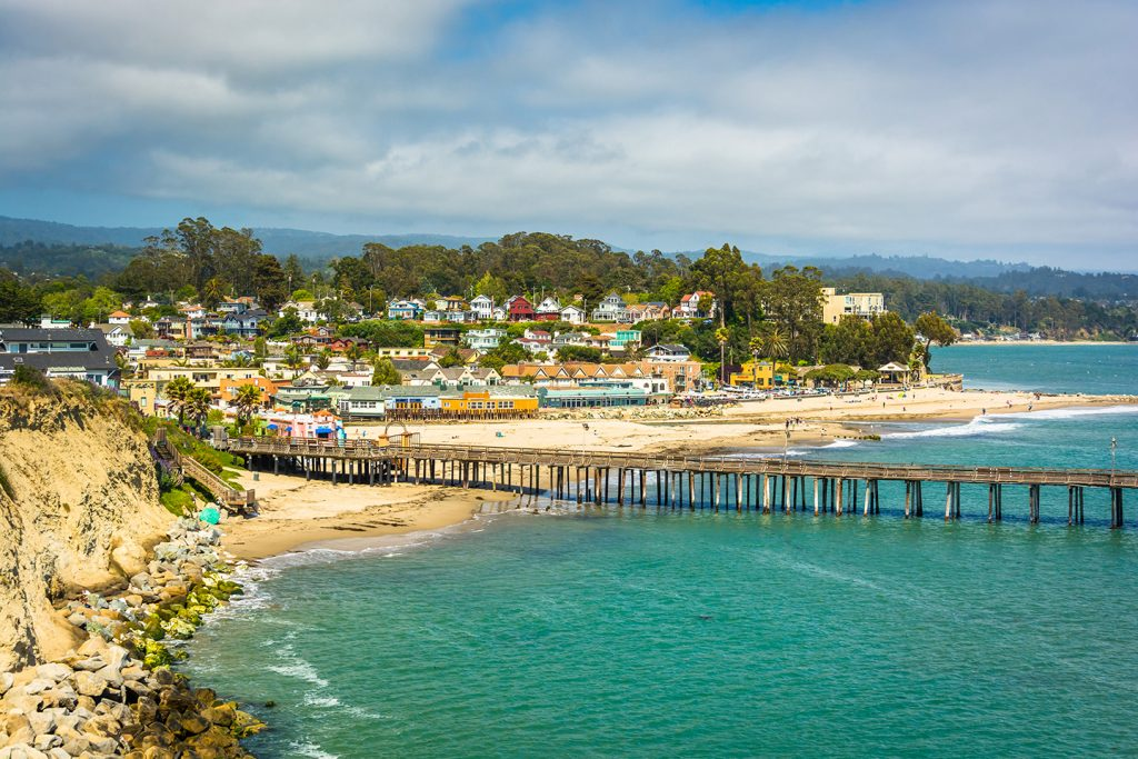 An aerial view of the unspoiled vacation spot of Capitola, CA, with a fishing pier stretching into the water and colorful houses in the distance