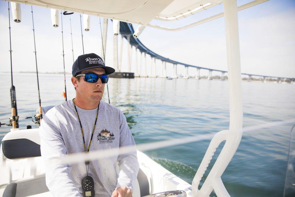 A charter captain piloting a boat near a bridge.