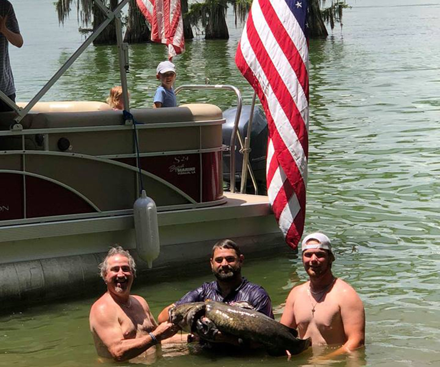 Three men holding a Catfish out of the water with a boat flying the American flag behind them