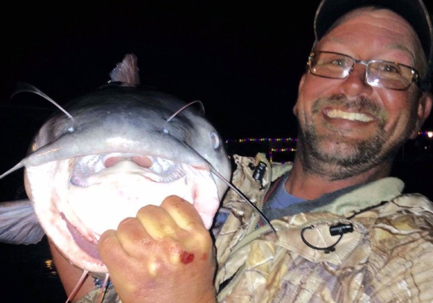 A smiling man wearing glasses holding a large Catfish with its mouth open.
