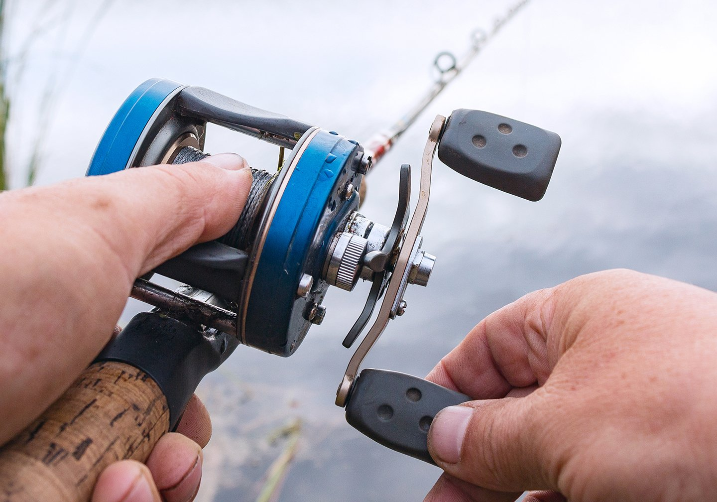 A baitcaster fishing reel being held near some water.