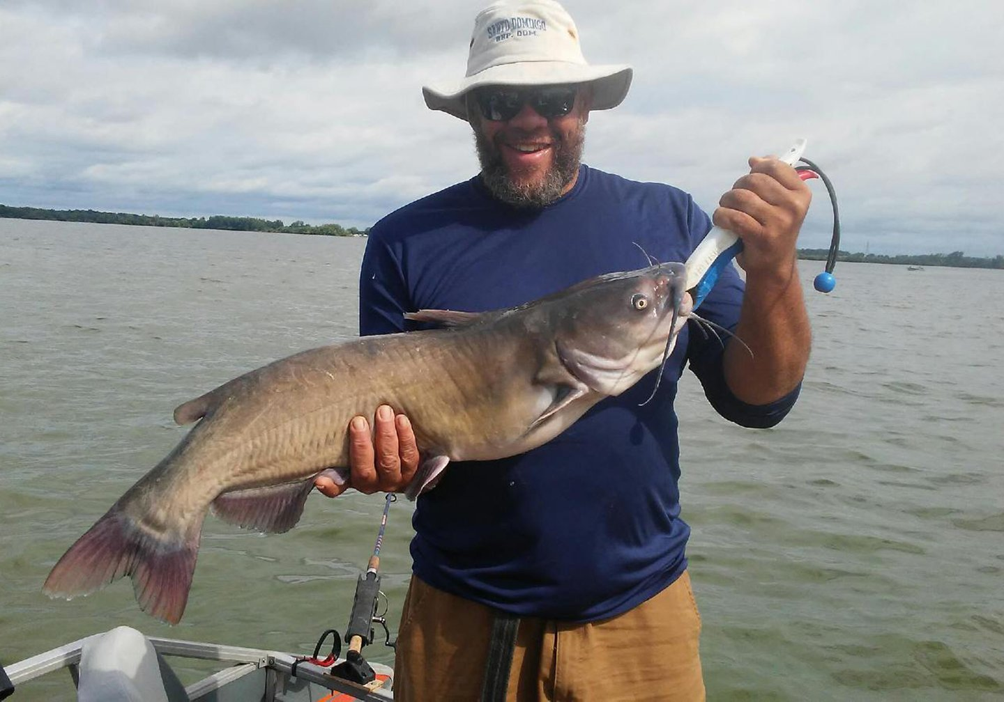 A smiling angler in a hat holding a Channel Catfish with water in the background