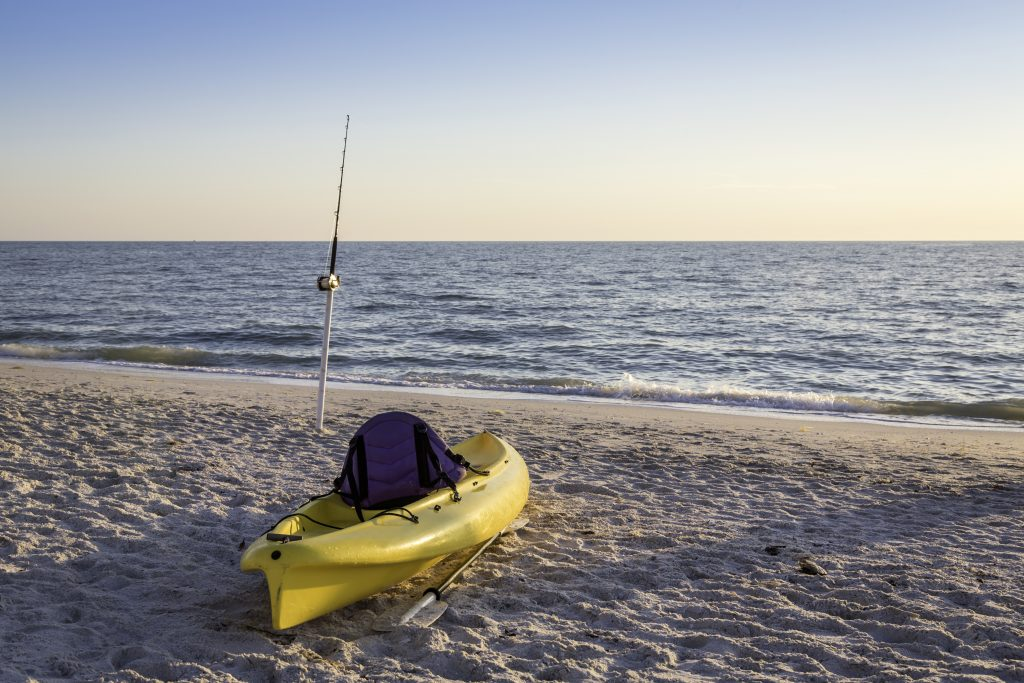 A yellow fishing kayak on a beach, with a surf fishing rod near the water behind it