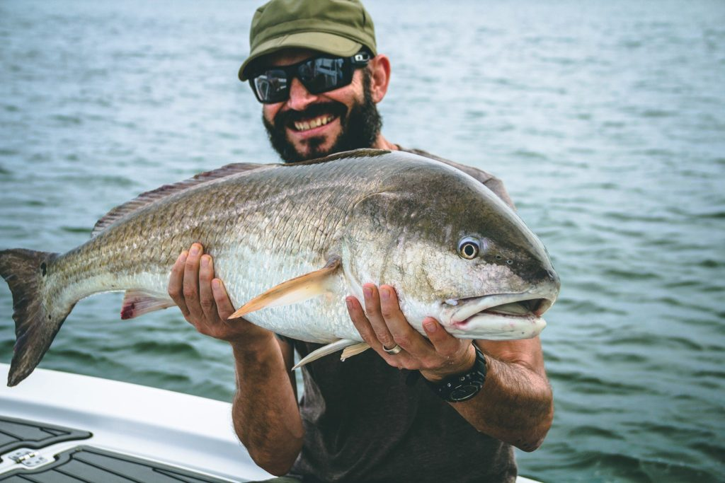 An angler holding a large Red Drum caught while fishing in Charleston, SC