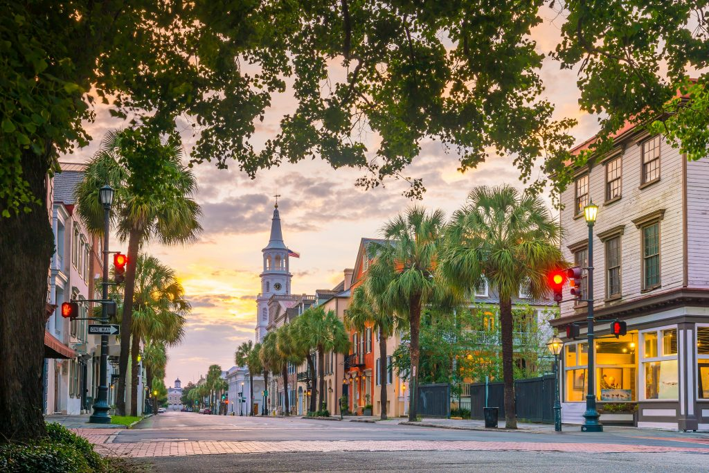 An old street in Charleson, SC, with Antebellum buildings and an old church in pink evening light