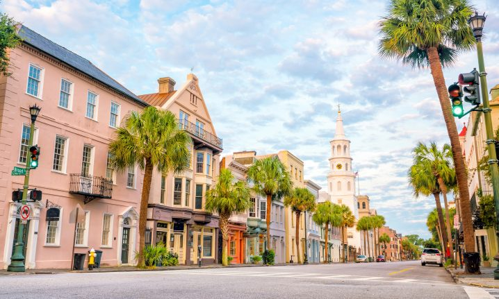 A historic street in Charleston, SC with palm trees and a blue sky