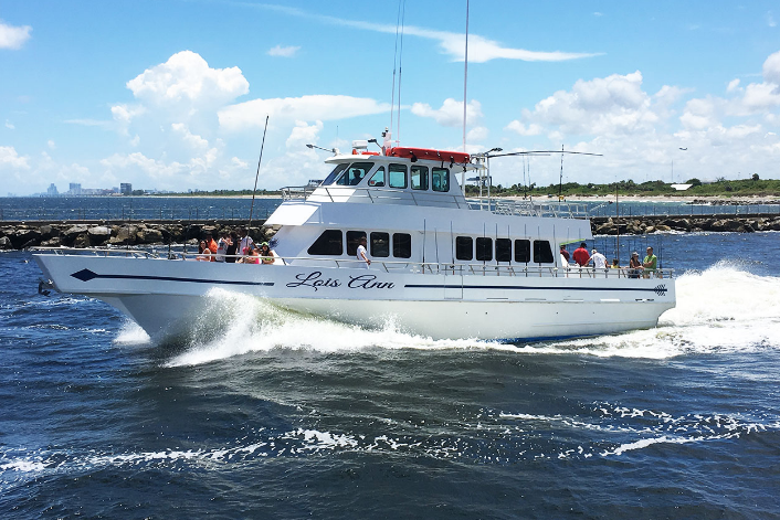 A large fishing charter cruising out of the harbor
