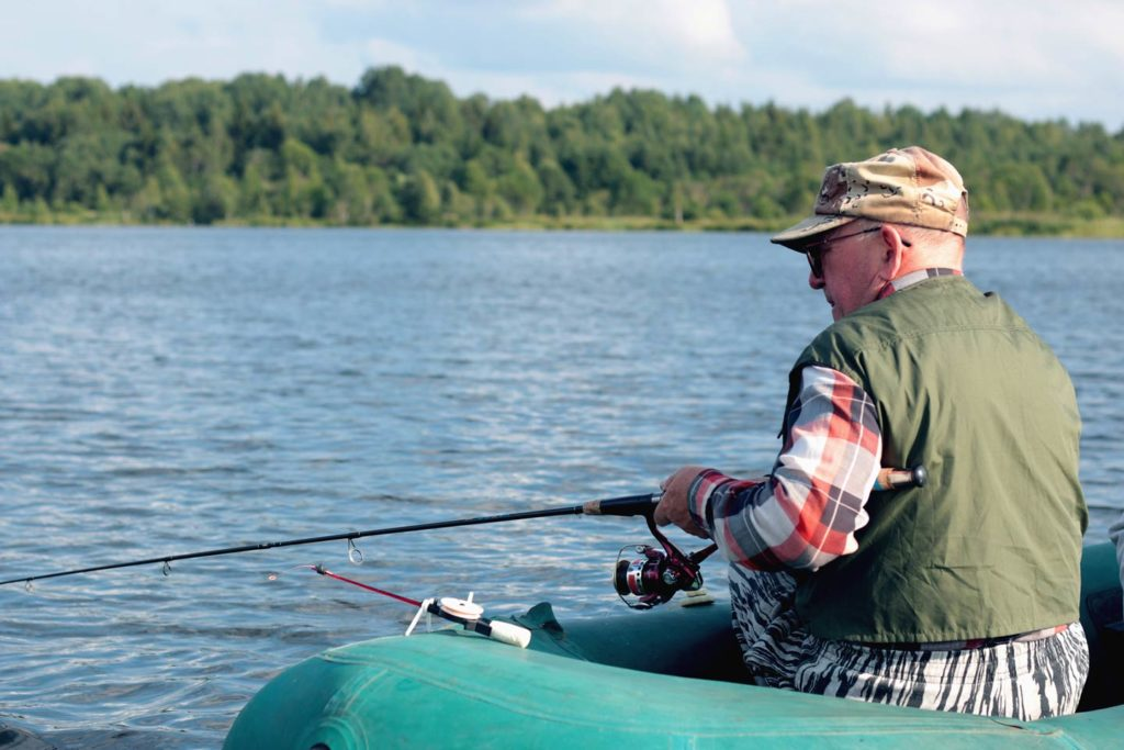 A male angler casts a spinning rod from a float boat.