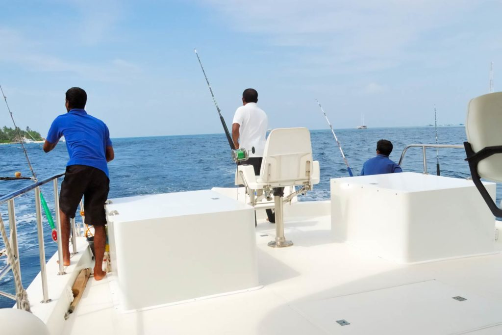 Three anglers on a charter boat in the Indian Ocean.