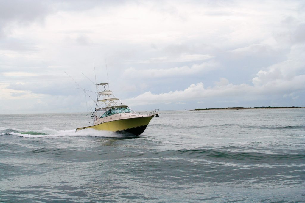 A charter boat cruising through choppy waters on a cloudy day