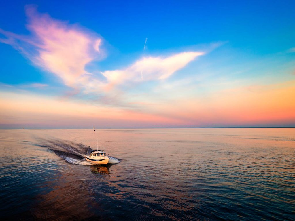 An aerial photo of Lake Superior with a boat on the water during sunset