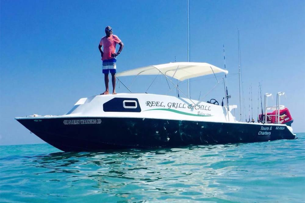 A man stands on the front of a fishing charter in Belize