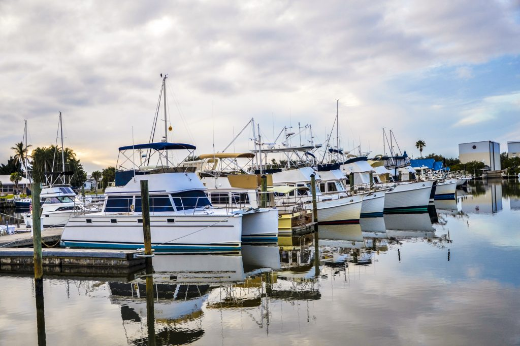 Large charter boats docked in a harbor, including a catamaran, the most stable type of boat