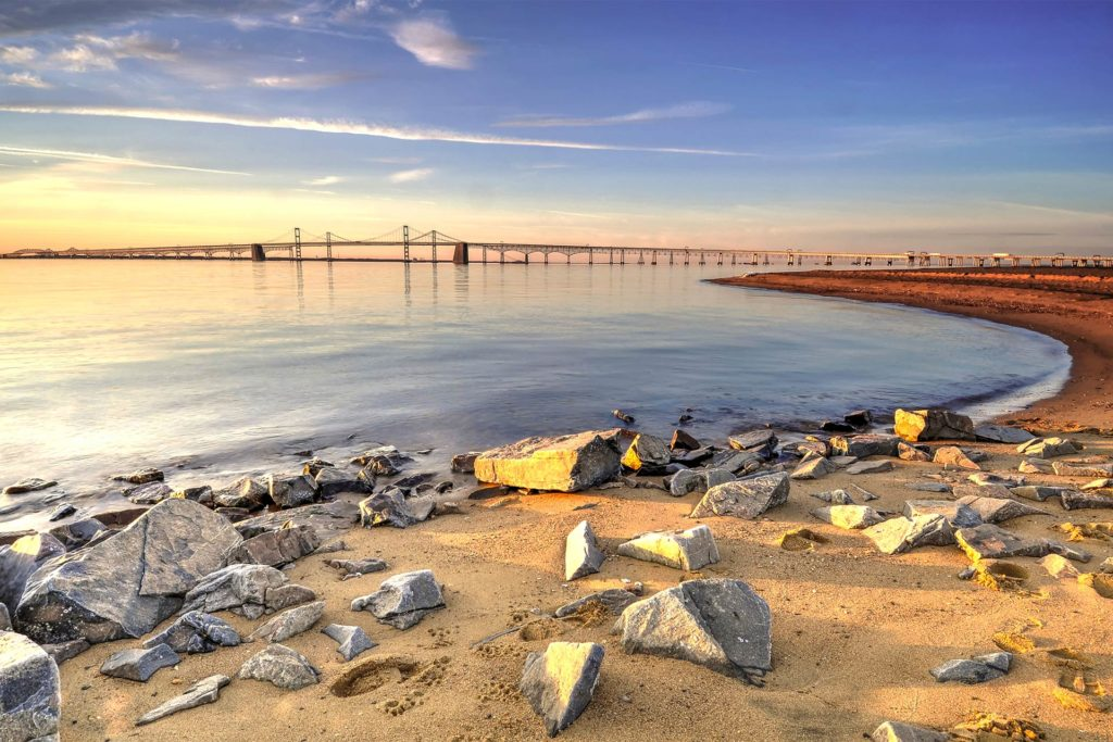 A view of the Chesapeake Bay Bridge at sunset, with a rocky beach in the foreground