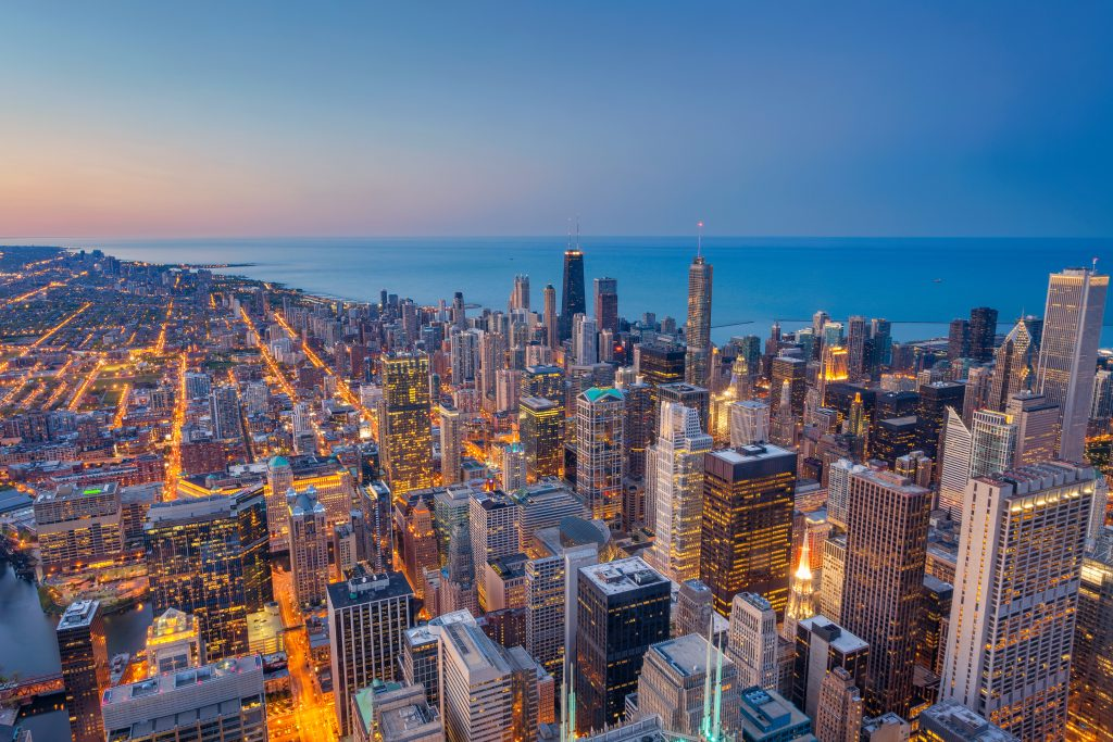 The Chicago skyline at dusk with Lake Michigan in the distance.