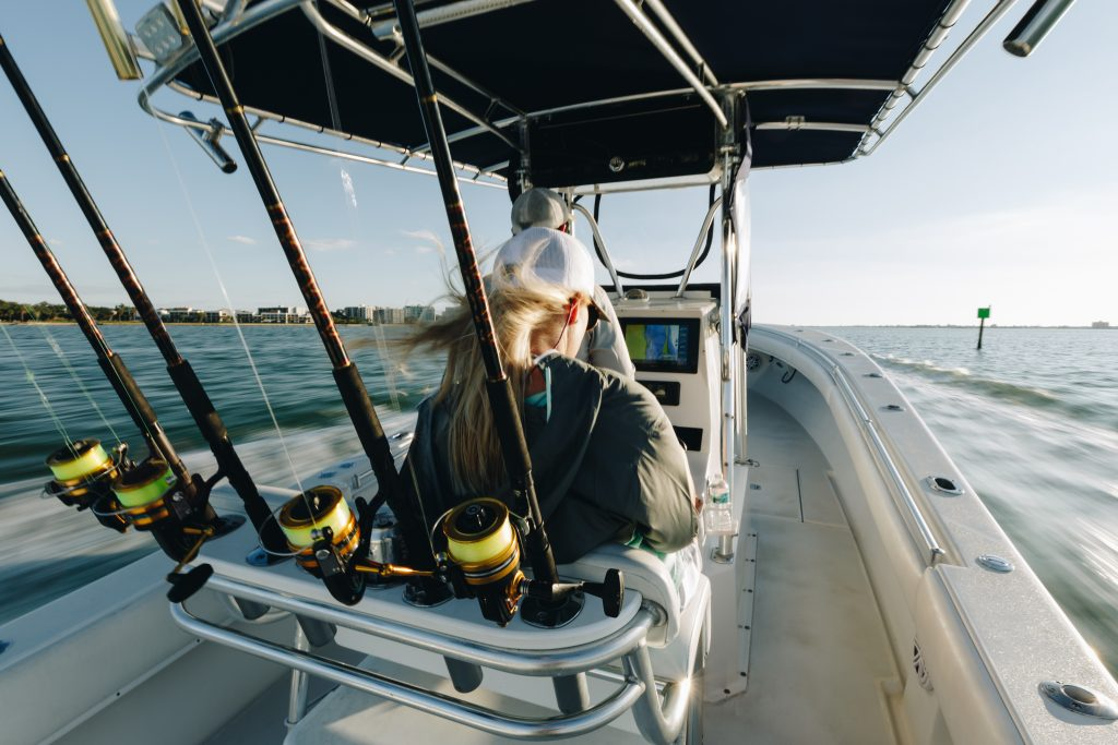 A man and a woman speeding offshore on a sportfishing boat