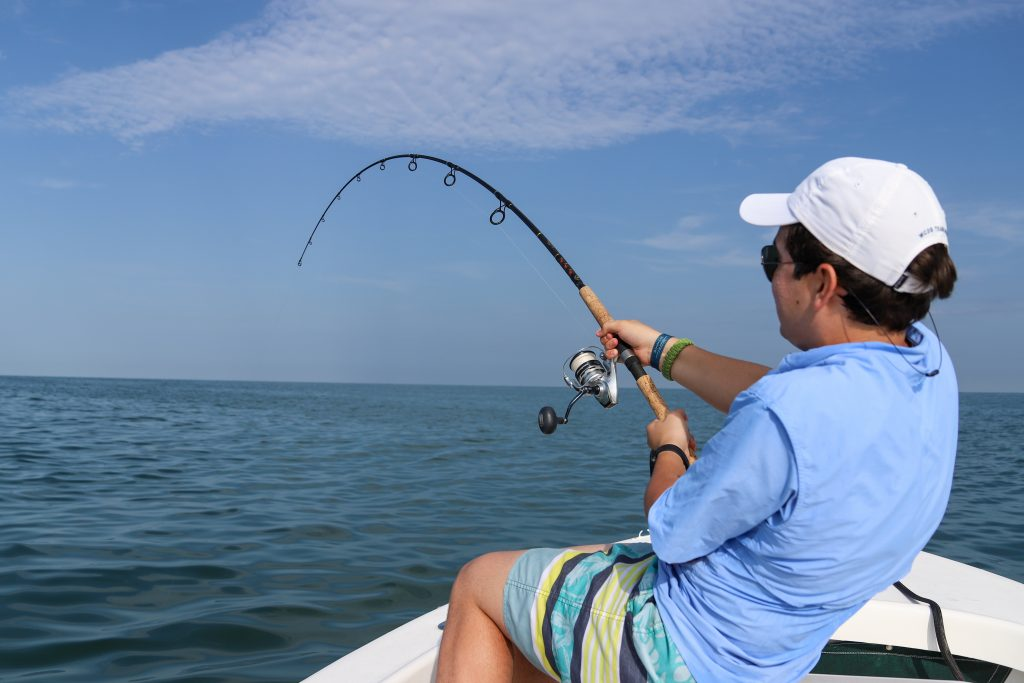 A man holding fishing on a boat. He is holding a rod which is bent from the strain of reeling in a big fish.