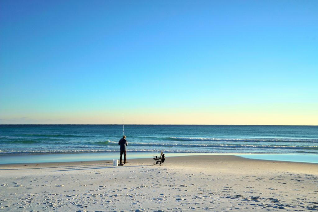 A man surf fishing on a white sandy beach in Clearwater, FL
