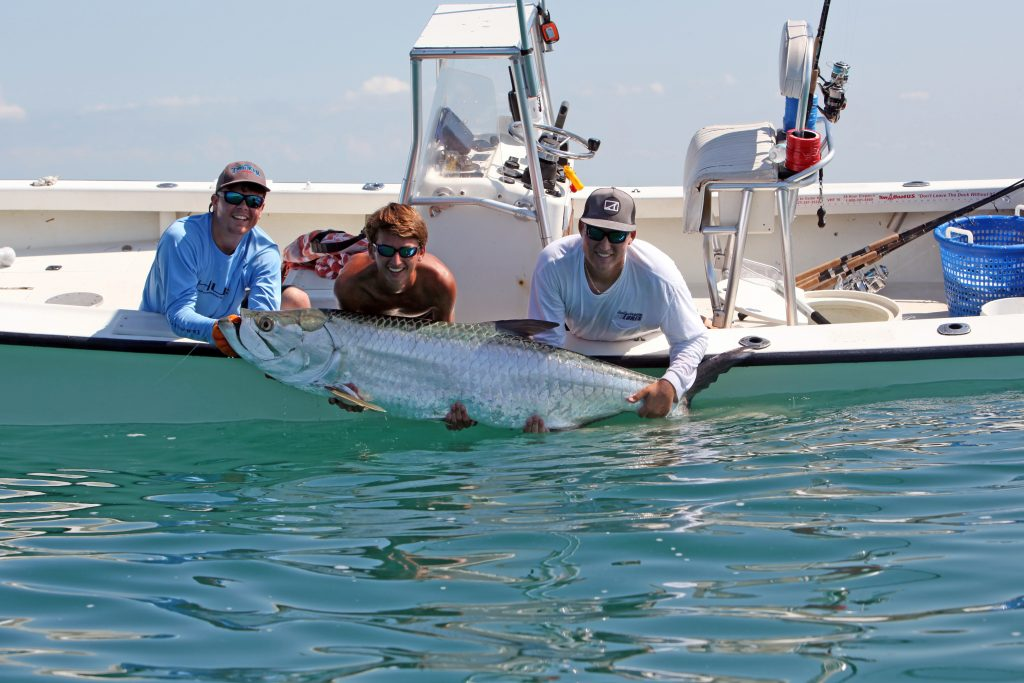A group of anglers leaning over the side of a boat to hold up a huge Tarpon caught while fishing in Clearwater, FL