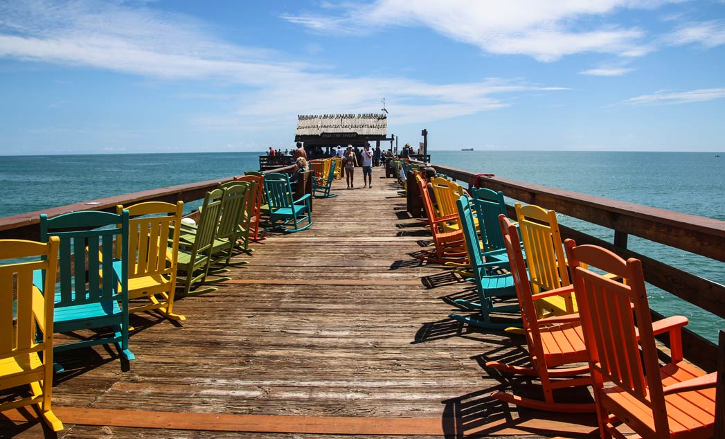 A view of multicolored chairs lining Cocoa Beach fishing pier
