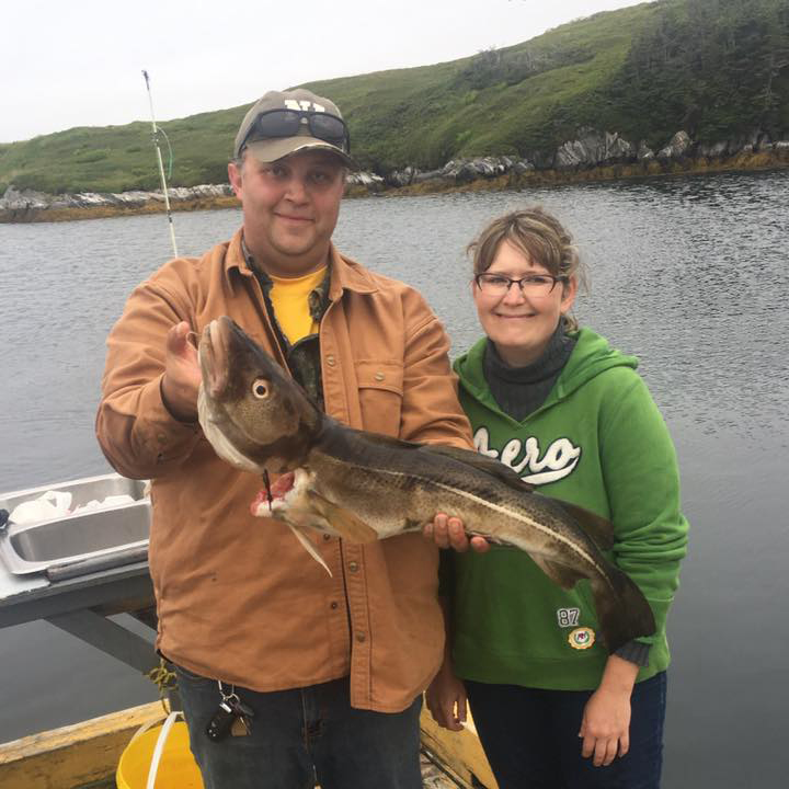 Two happy anglers holding a Cod