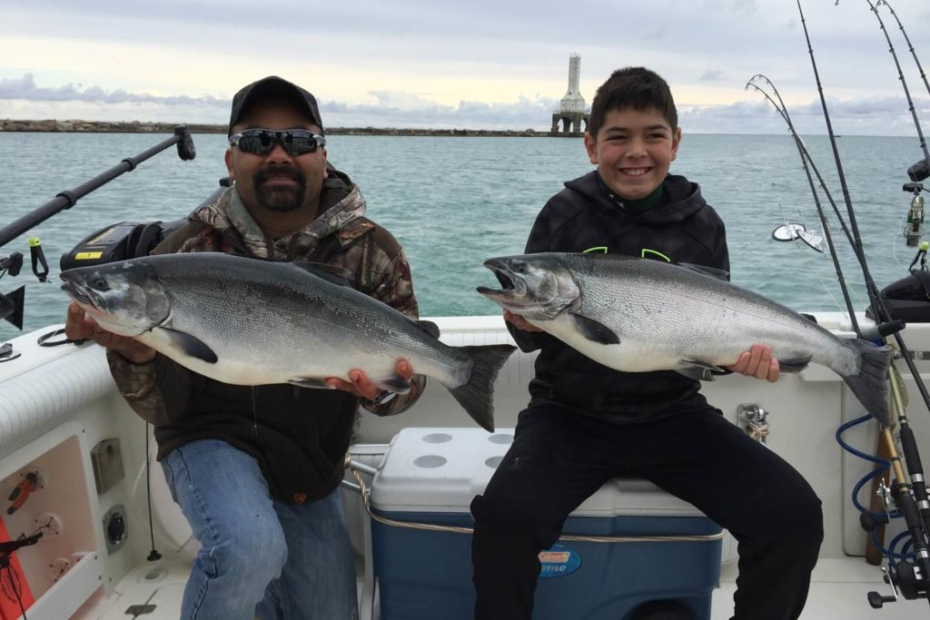 A man and a boy sit on a charter boat holding a large Coho Salmon each.