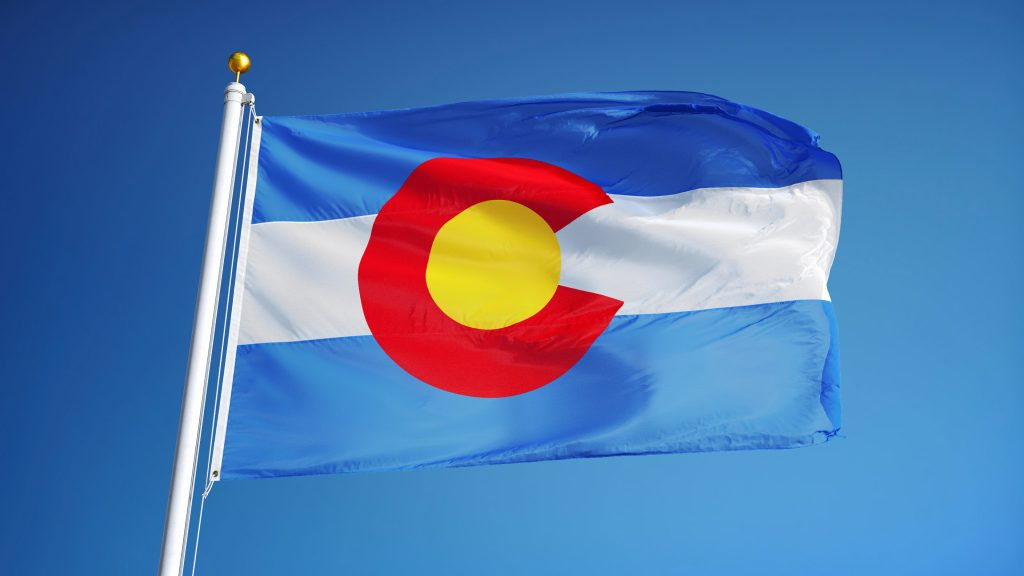 The Colorado state flag flying with blue sky behind