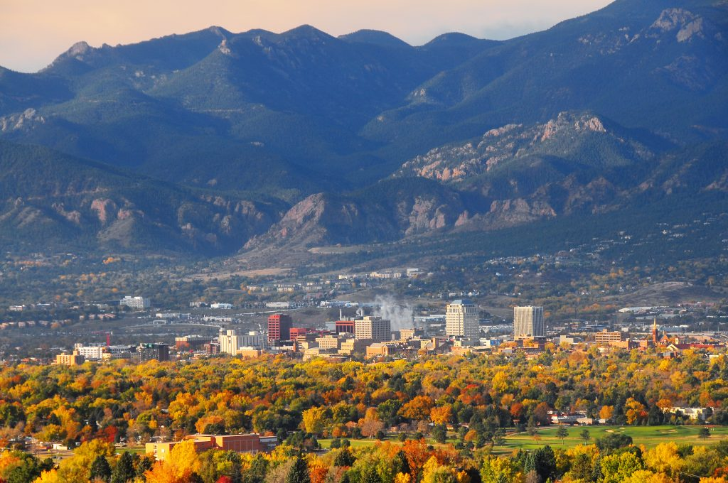 A view across yellow forest to Colorado Springs, one of the best US fishing cities. The Rocky Mountains rise in the distance.