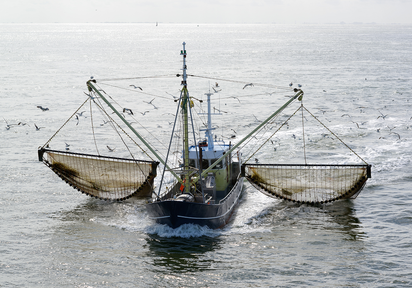 A commercial fishing boat with its nets extended.