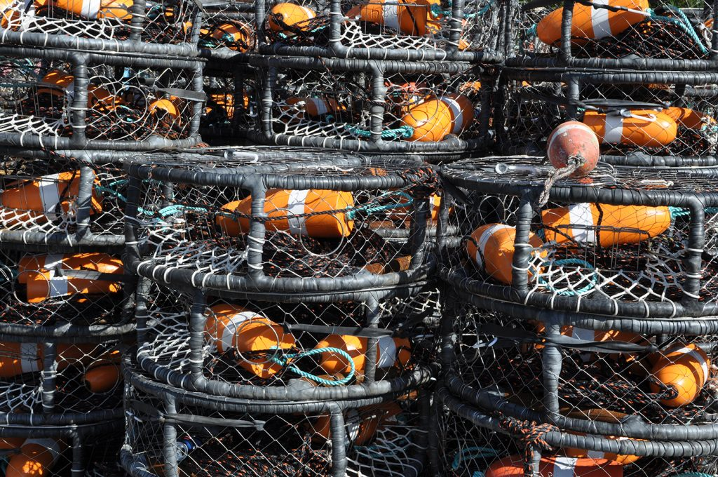A stack of black commercial crab pots with orange floats.