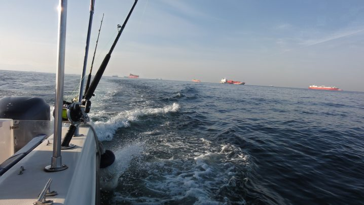 The back of a charter boat with a fishing rod in the foreground and red oil tankers in the distance
