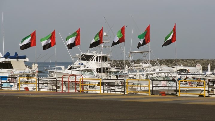 A view of Fujairah sportfishing marina with charter boats and 7 United Arab Emirates flags