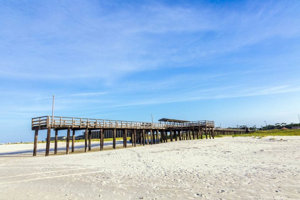 Dauphin Island pier on a sunny day, with the beach and blue skies in shot