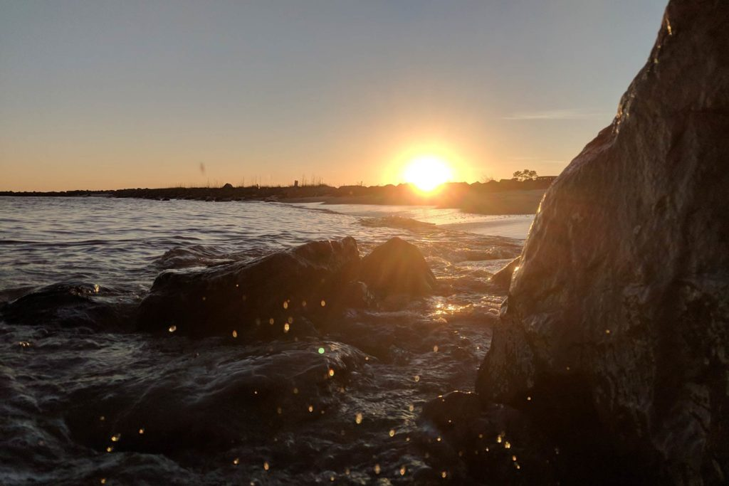 Dauphin Island's rocky shoreline waters at sunset